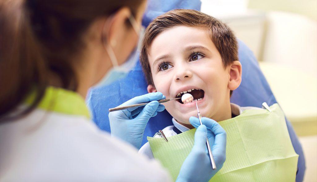 Стоматолог осматривает зубы у ребёнка.
